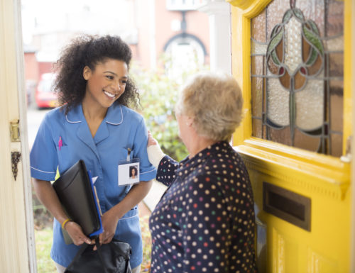 A female nurse or community care worker is at the front door of her senior female patient and saying hello. She is wearing a blue nurses tunic , and holding a medicines bag . She is wearing an ID badge with her profile photo already on it . The senior patient has her back to us at the front door . In the background a residential street can be seen defocussed .
