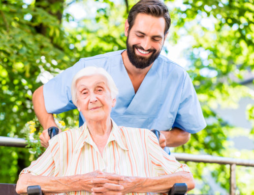 Geriatric nurse pushing senior lady in wheel chair thru home